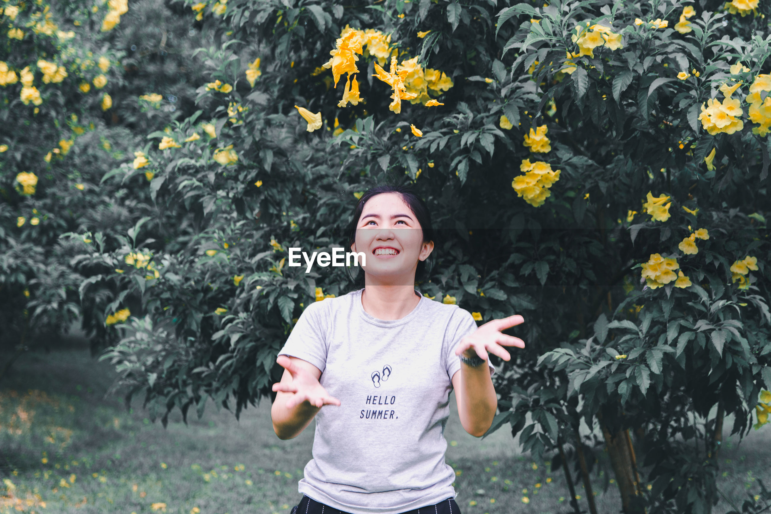 Smiling woman throwing flowers while standing against trees