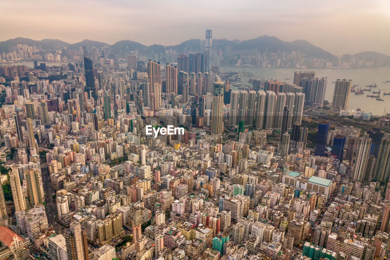cityscape, city, sky, architecture, building exterior, built structure, modern, skyscraper, crowd, building, mountain, nature, office building exterior, urban skyline, challenge, opportunity, crowded, vitality, strength