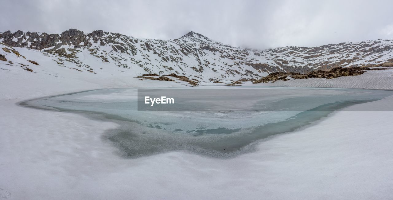 Scenic View Of Lago Della Vacca And Snow Covered Mountains