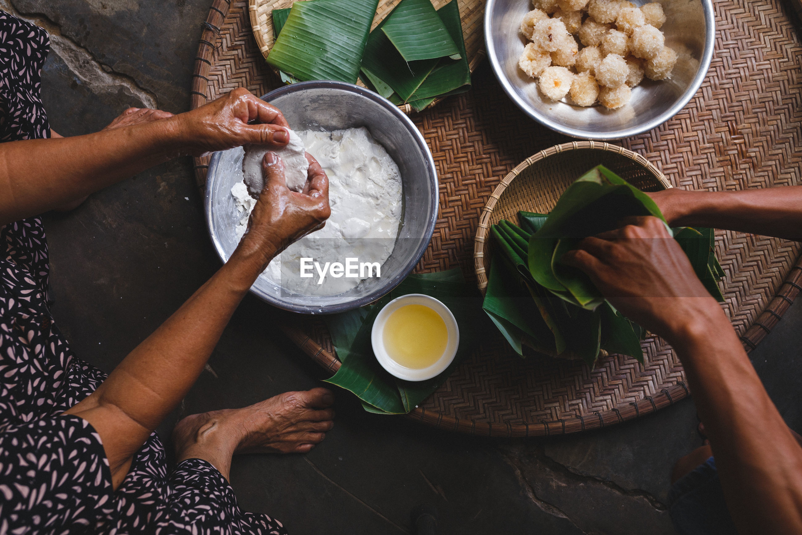 Low section of man and woman making rice cakes in cone
