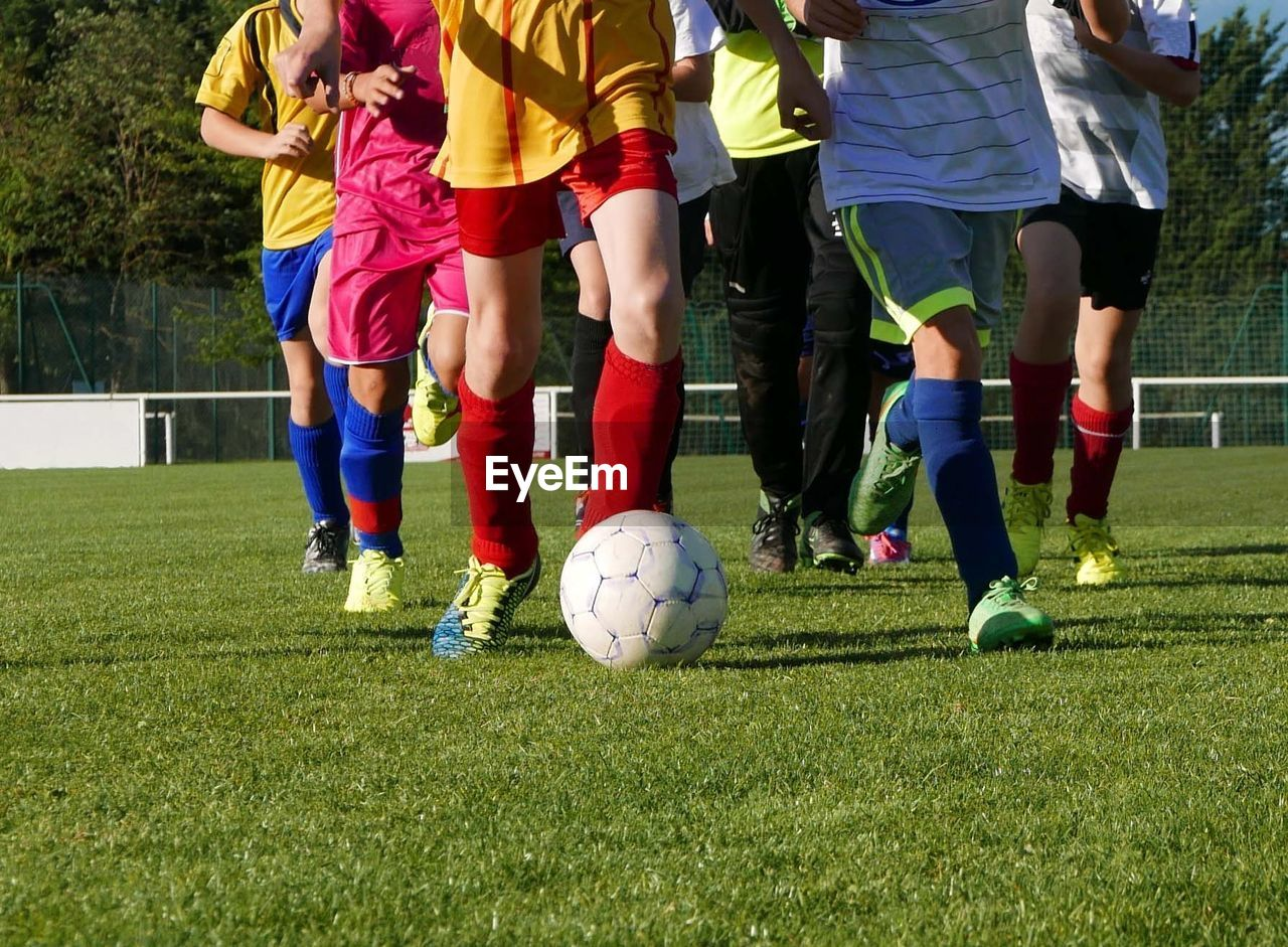 Low Section Of Teenage Boys Playing Soccer On Field