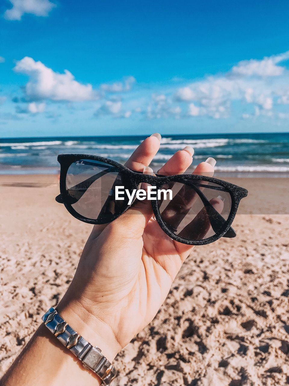 sea, beach, land, sky, water, glasses, one person, hand, real people, horizon over water, sunglasses, human hand, horizon, human body part, leisure activity, personal perspective, day, nature, lifestyles, fashion, outdoors, body part, personal accessory