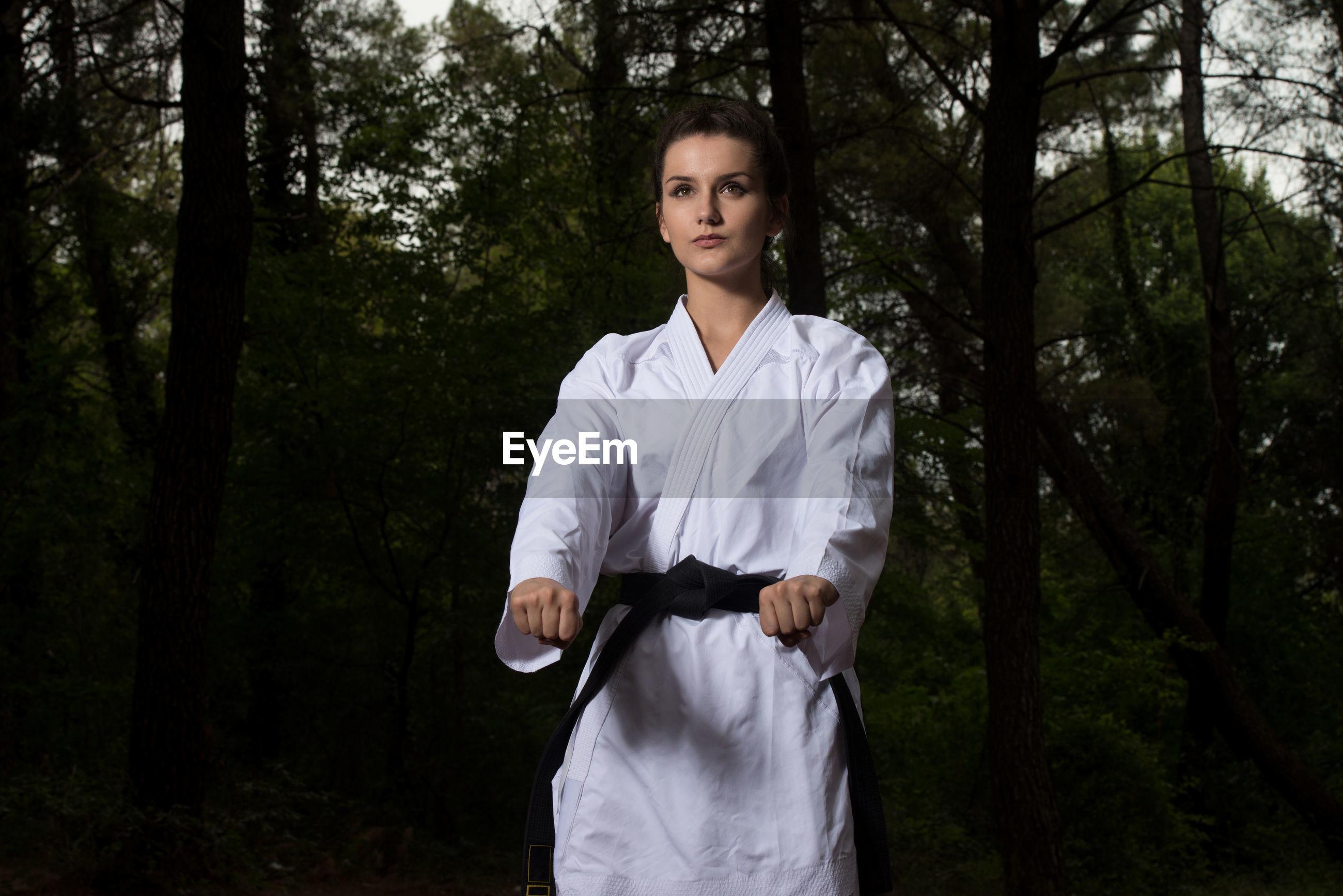 Karate woman standing against trees