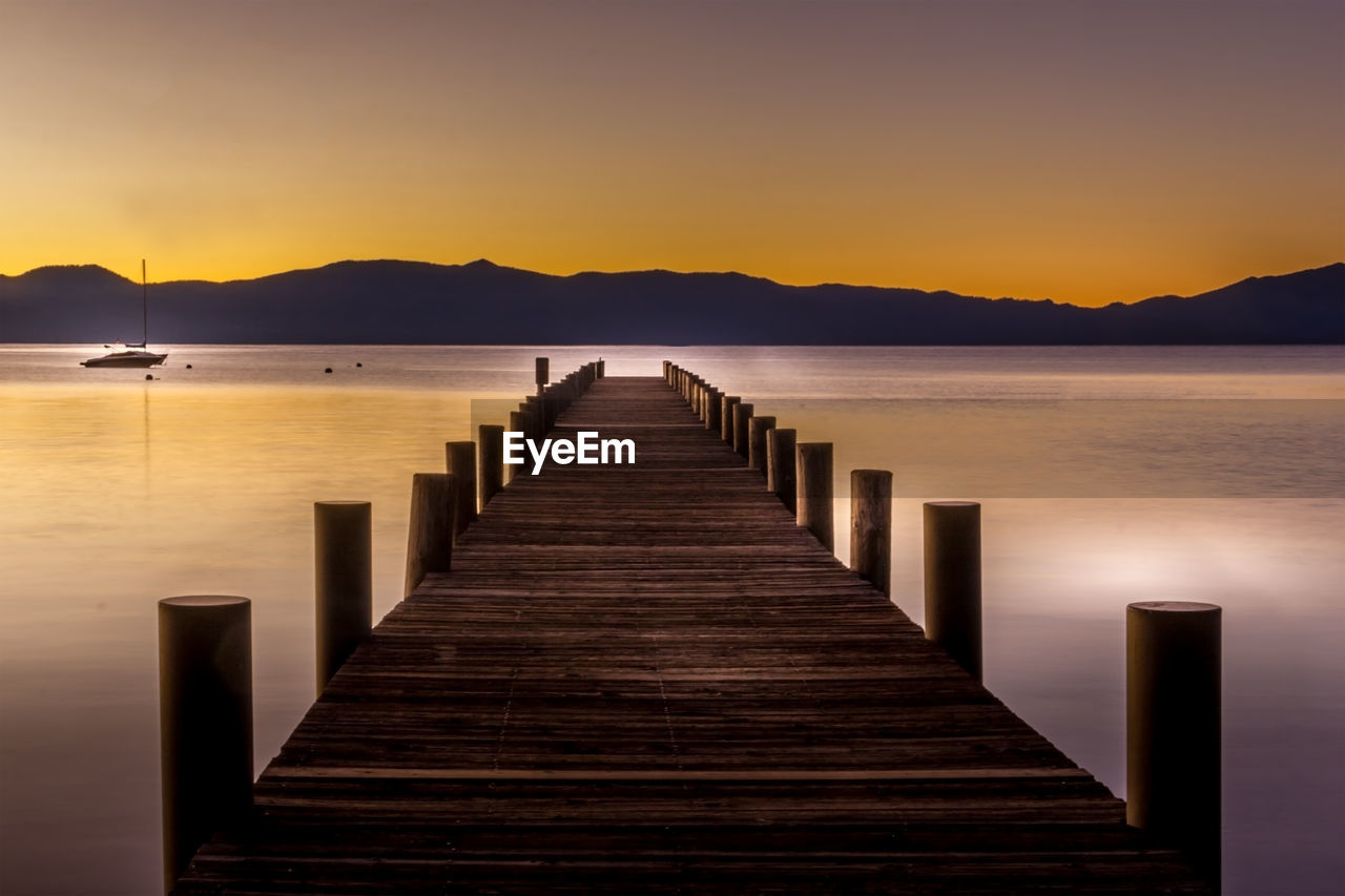 sky, water, tranquility, beauty in nature, tranquil scene, scenics - nature, the way forward, direction, sunset, lake, nature, wood - material, no people, pier, mountain, jetty, clear sky, idyllic, outdoors, wood paneling, long, wooden post