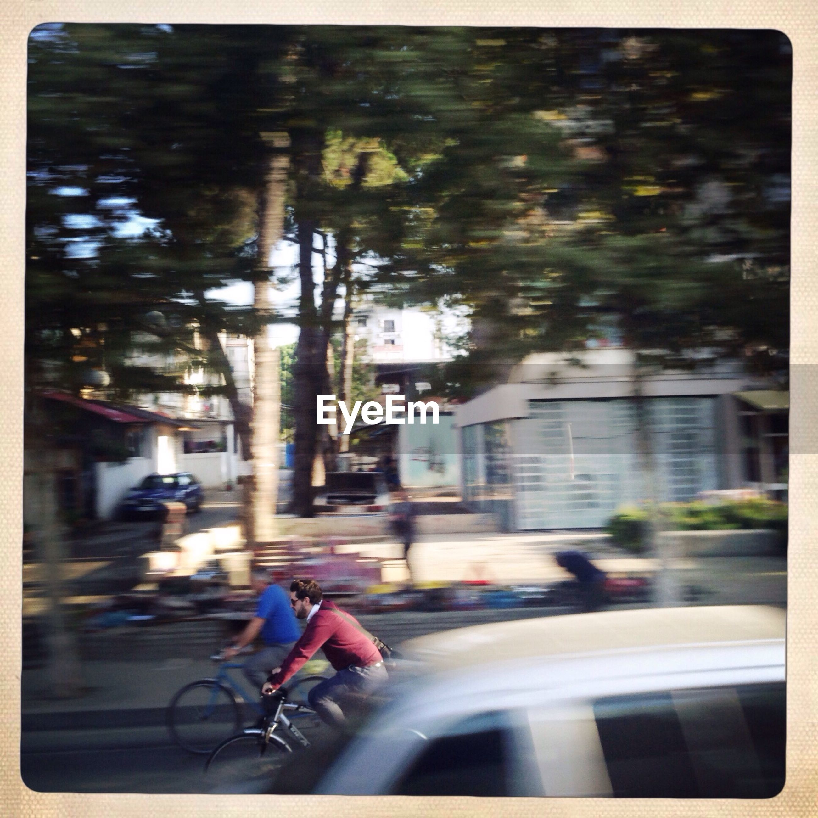 Blurred motion of people riding vehicles on street
