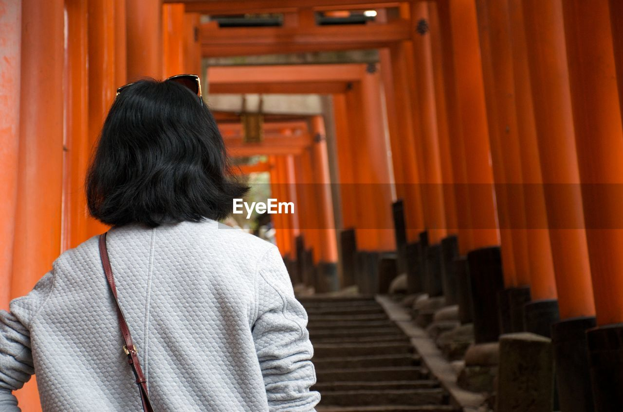 rear view, orange color, real people, place of worship, architecture, one person, religion, belief, spirituality, built structure, lifestyles, in a row, building, standing, women, black hair, waist up, shrine, hairstyle