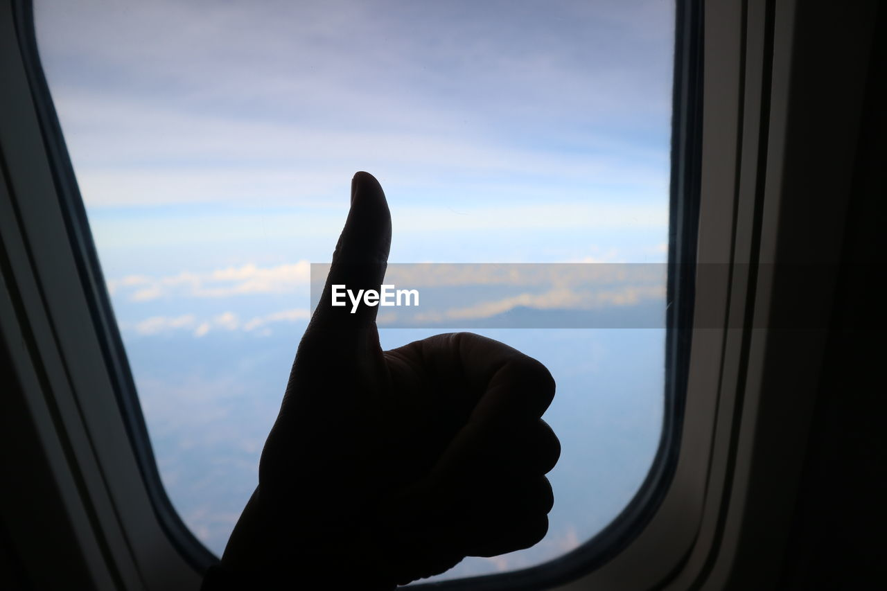 Close-up of silhouette hand gesturing against airplane window
