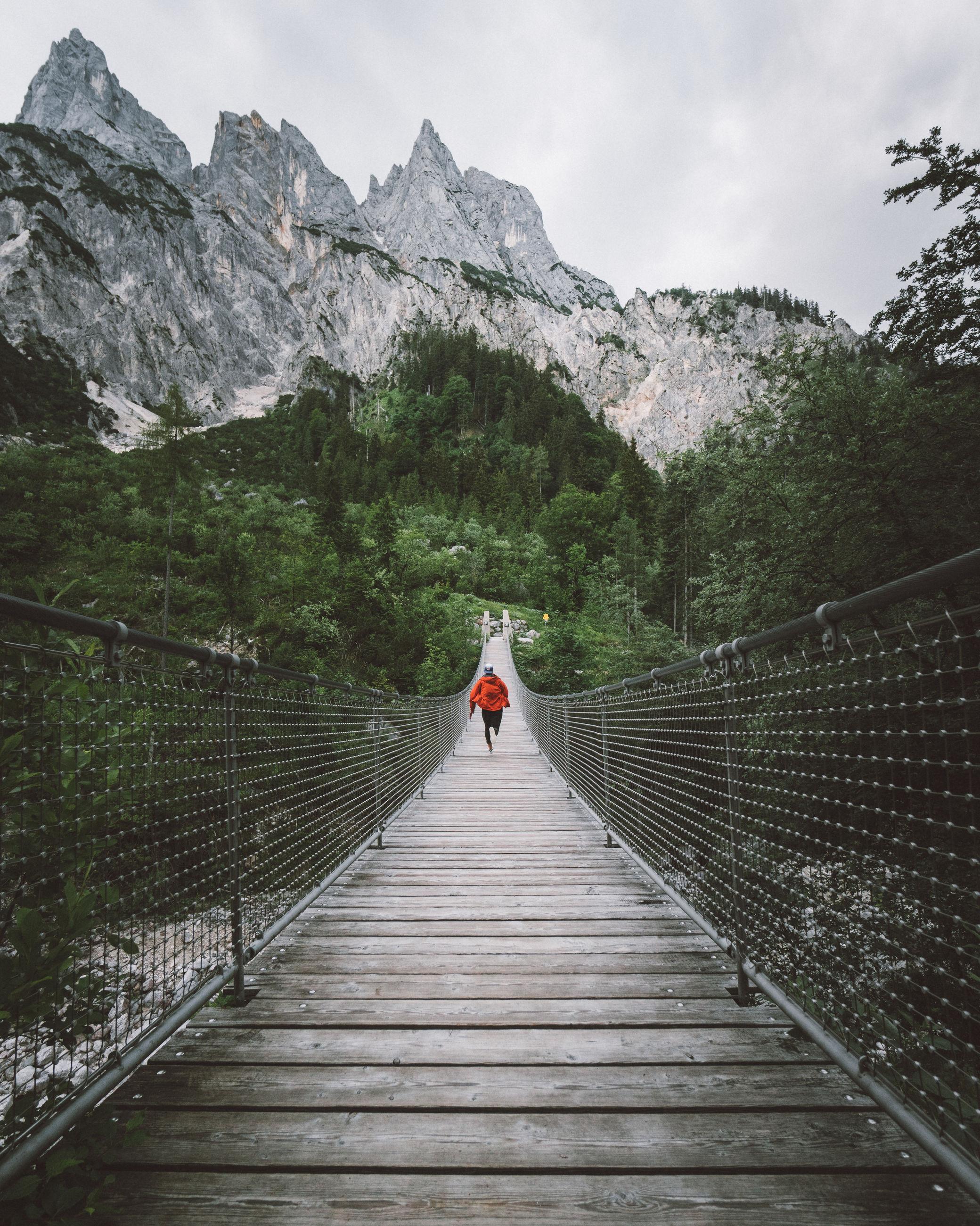 Man running on footbridge against mountains