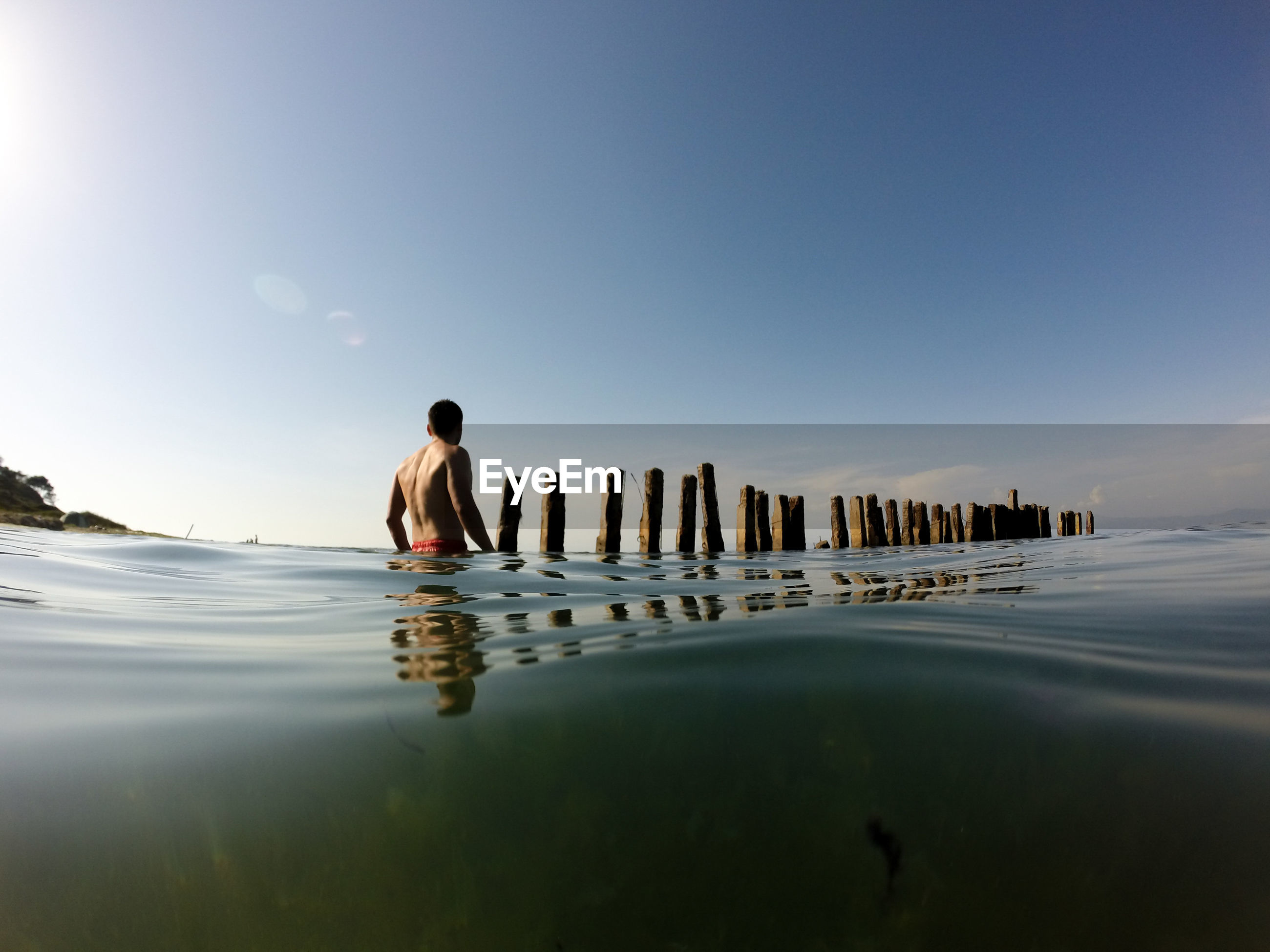 Water surface shot of shirtless man wading in sea against sky