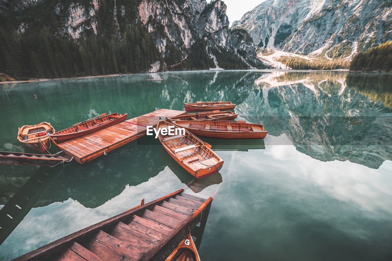 High Angle View Of Boats Moored On Lake By Mountains