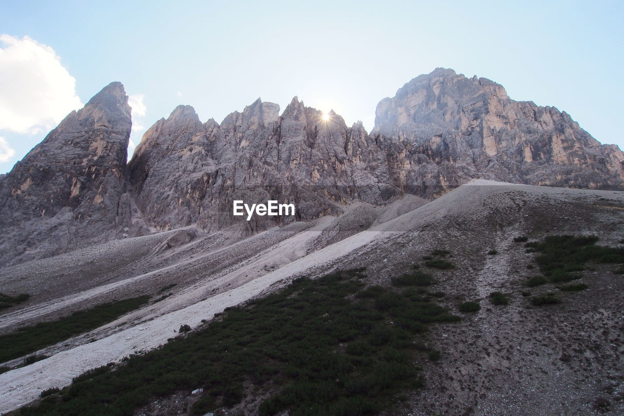 mountain, sky, environment, landscape, beauty in nature, scenics - nature, mountain range, nature, day, tranquil scene, no people, tranquility, non-urban scene, land, rock, geology, mountain peak, road, transportation, outdoors, arid climate, formation, climate, eroded