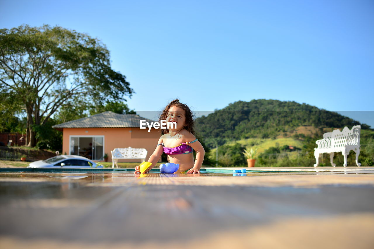 Portrait Of Cute Girl In Swimming Pool Against Clear Blue Sky