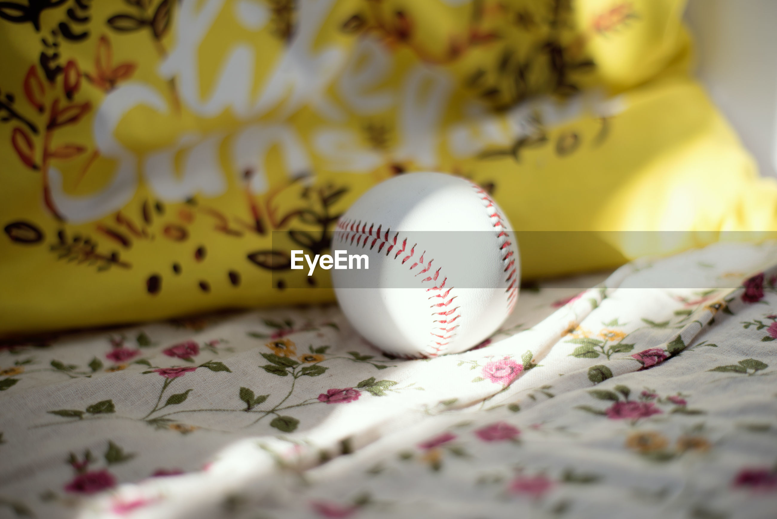 baseball, baseball - ball, indoors, selective focus, yellow, sports, no people, pattern, pink, ball, furniture, flower, close-up, floral pattern, bed