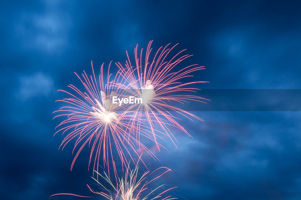 firework, event, arts culture and entertainment, illuminated, celebration, sky, motion, night, firework display, exploding, long exposure, low angle view, glowing, nature, blurred motion, no people, light, firework - man made object, outdoors, cloud - sky, sparks, new year's eve
