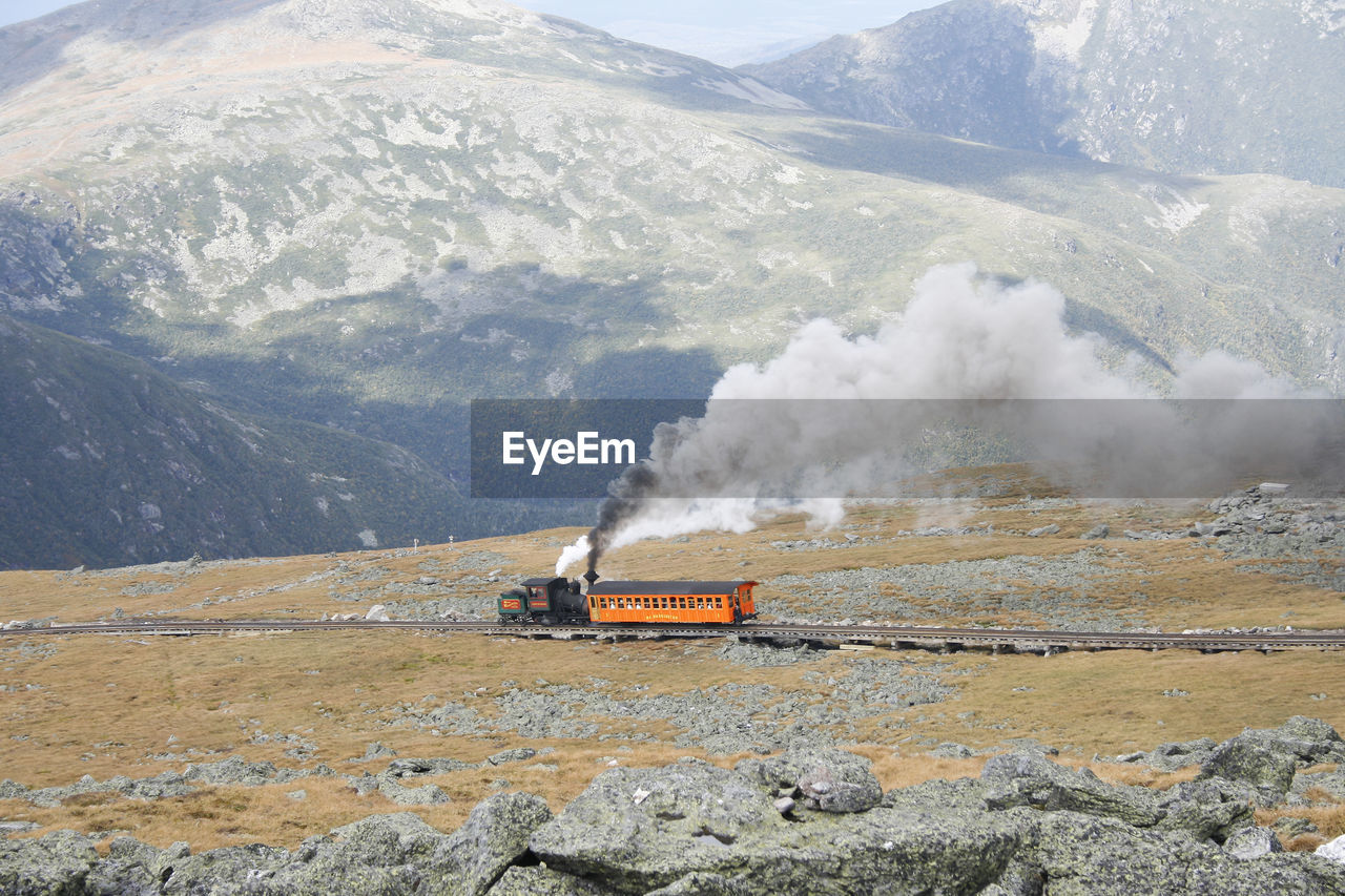 mountain, mode of transportation, smoke - physical structure, steam train, day, environment, transportation, train, rail transportation, public transportation, train - vehicle, nature, beauty in nature, no people, non-urban scene, scenics - nature, emitting, motion, mountain range, outdoors, pollution, air pollution