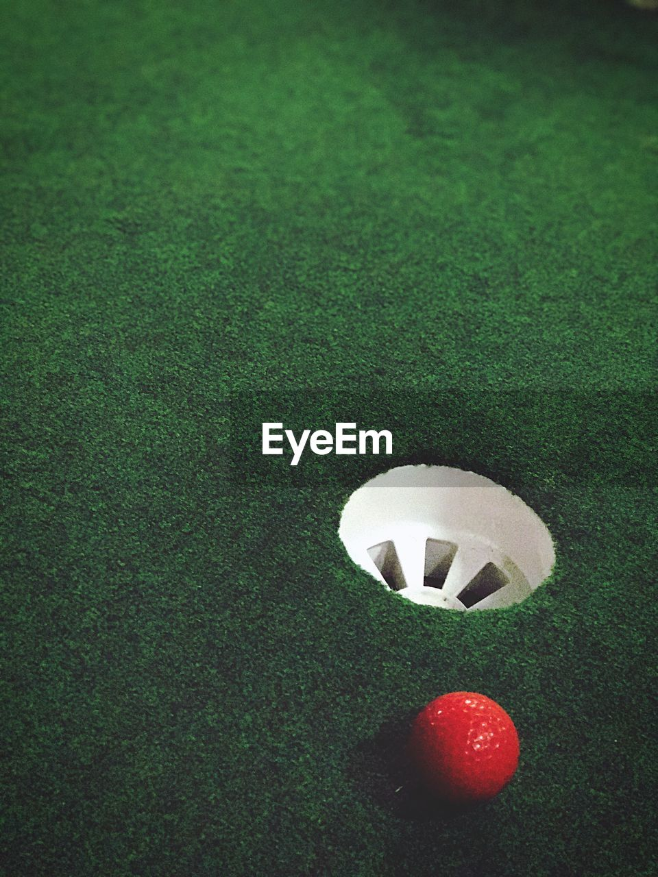 sport, grass, ball, golf ball, green color, golf, green - golf course, turf, golf course, lawn, playing field, competitive sport, red, leisure games, no people, tee, competition, soccer field, close-up, day, outdoors, snooker, pool ball