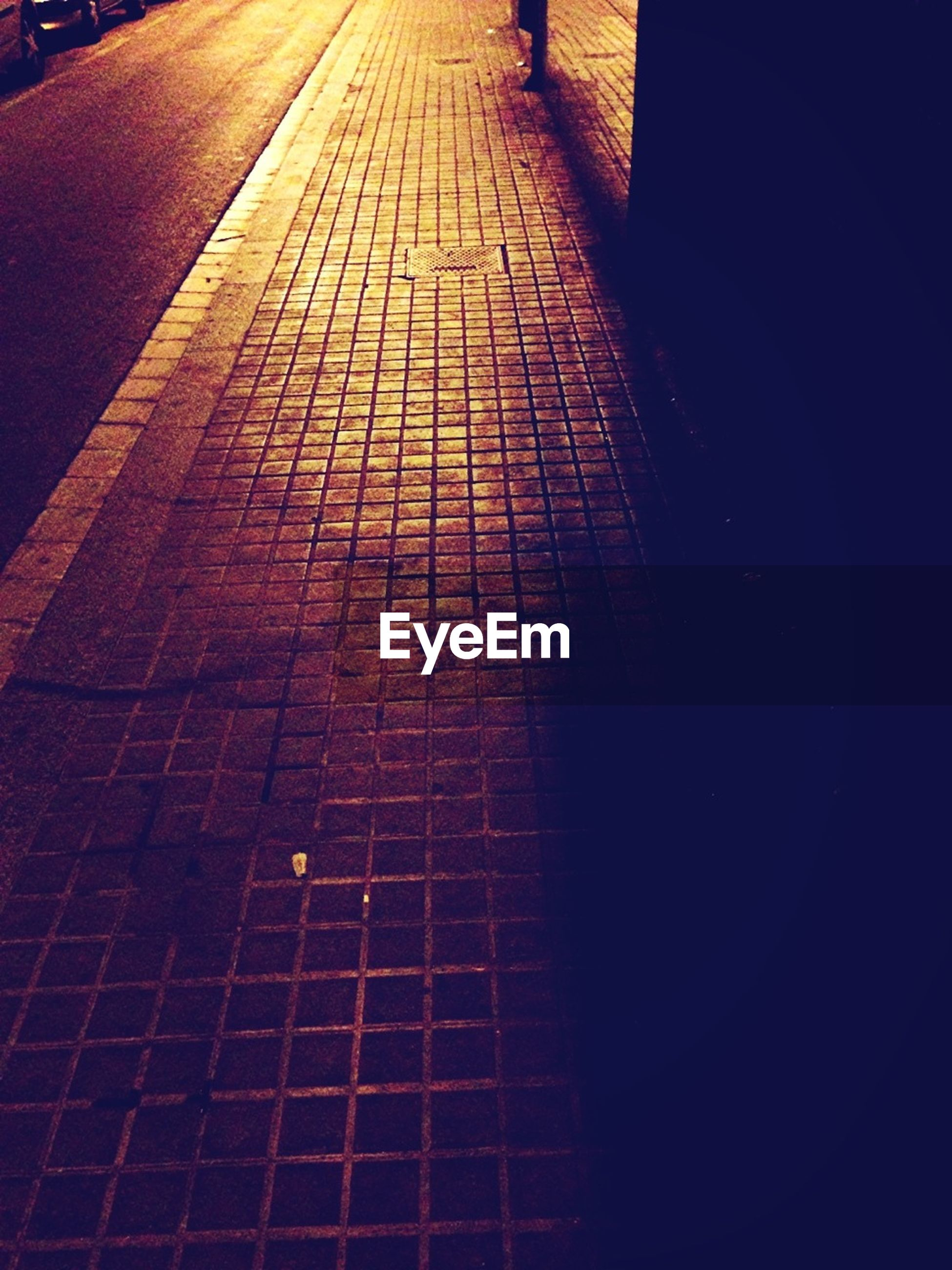 Low angle view of sidewalk at night