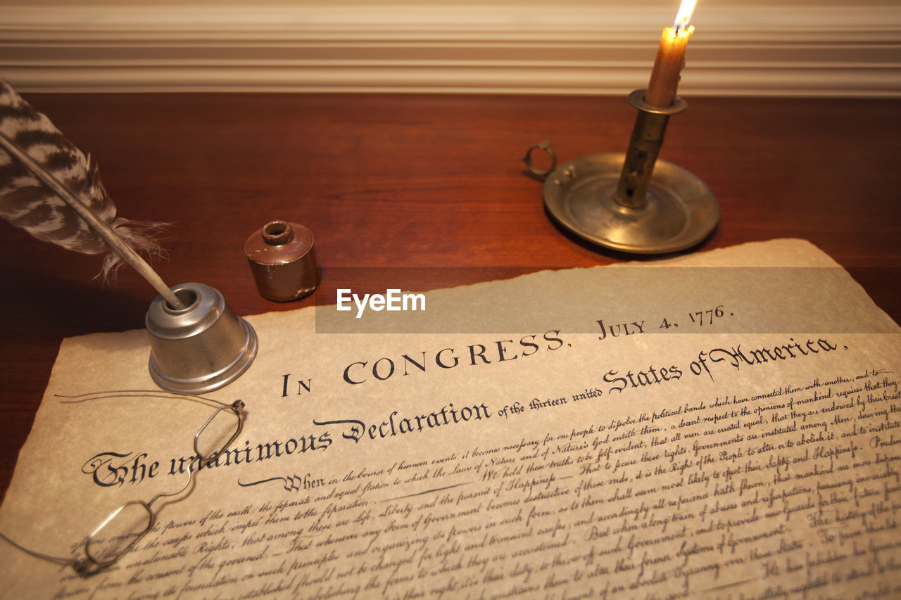 Lit candle on declaration of independence at table