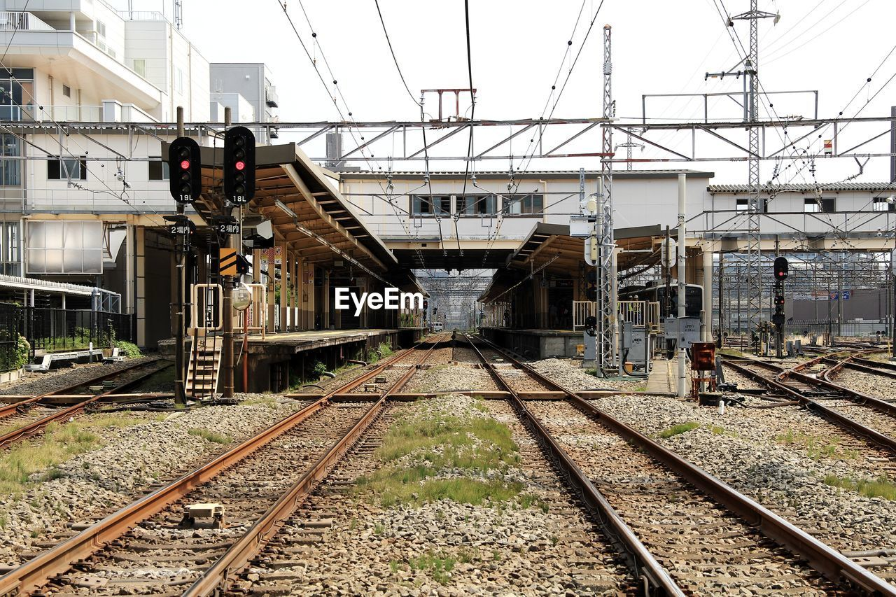 rail transportation, railroad track, track, transportation, architecture, built structure, building exterior, nature, day, mode of transportation, connection, sky, no people, public transportation, direction, outdoors, the way forward, electricity, train, cable, power supply, long