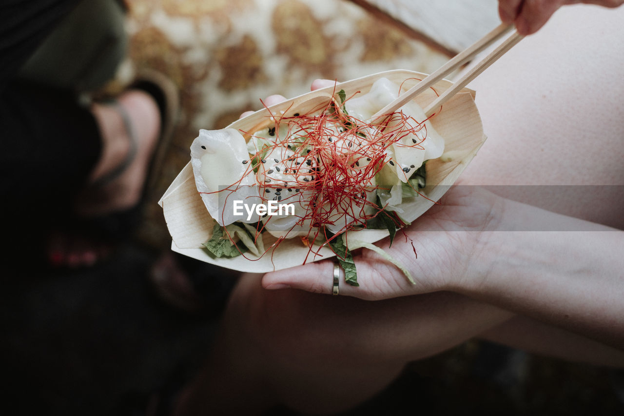 Cropped Hand Of Woman Having Food With Chopsticks