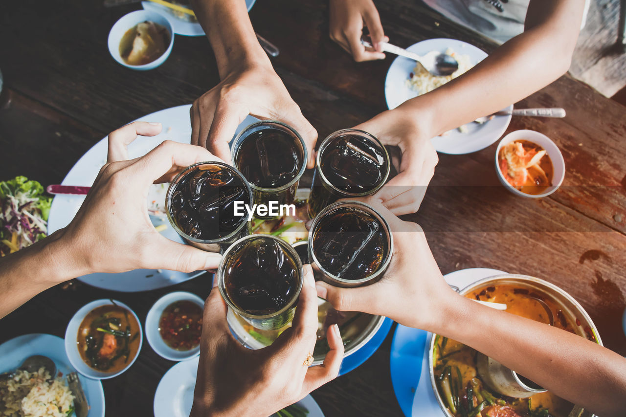 High Angle View Of People Toasting Drinking Glasses Over Table