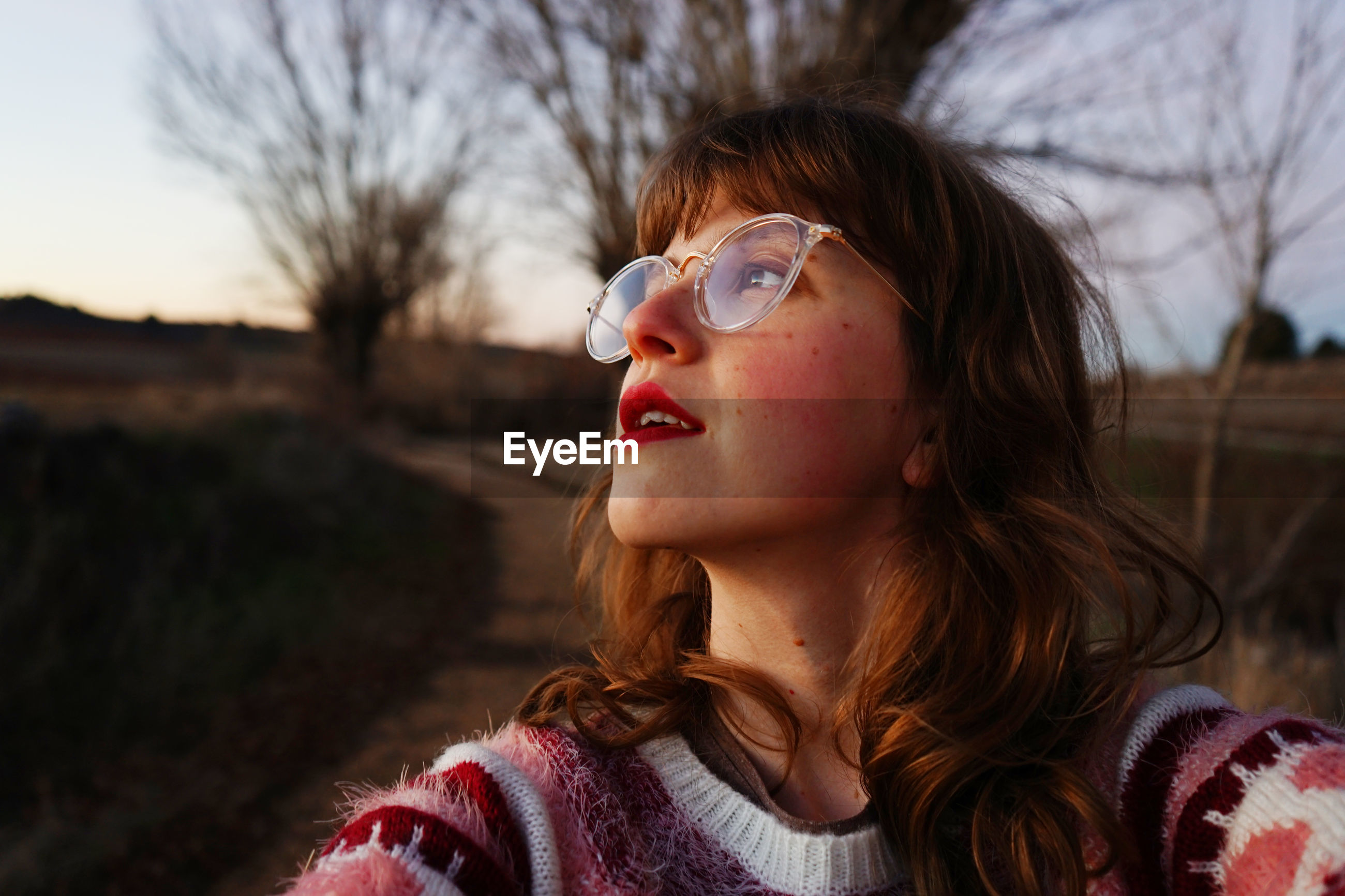 Close-up of young woman wearing eyeglasses against bare trees