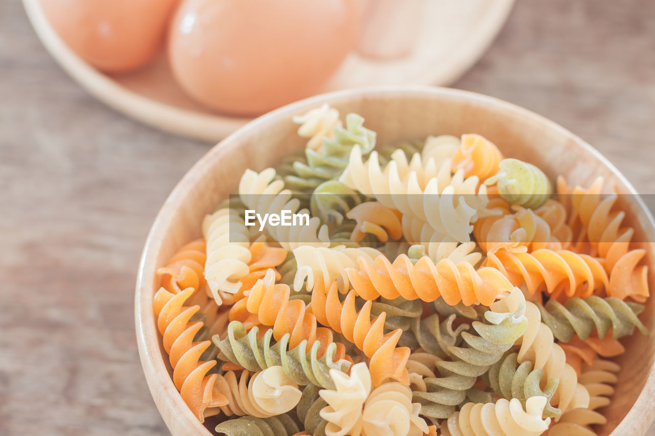 Close-up of raw pasta and eggs on table