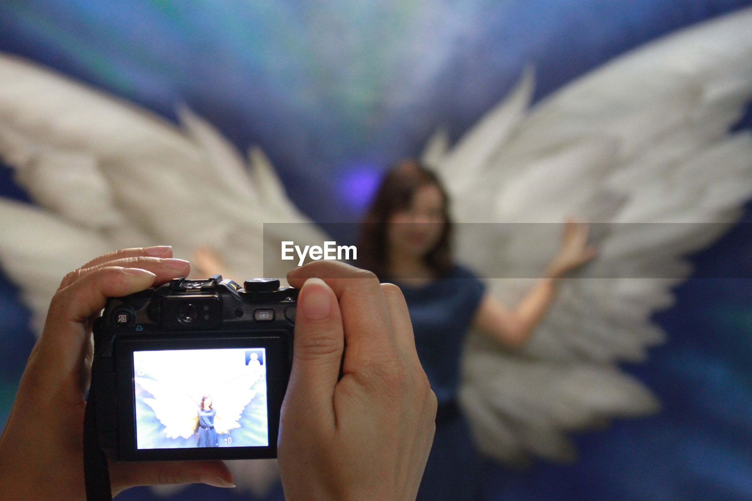 Cropped image of hands photographing woman wearing wing costume