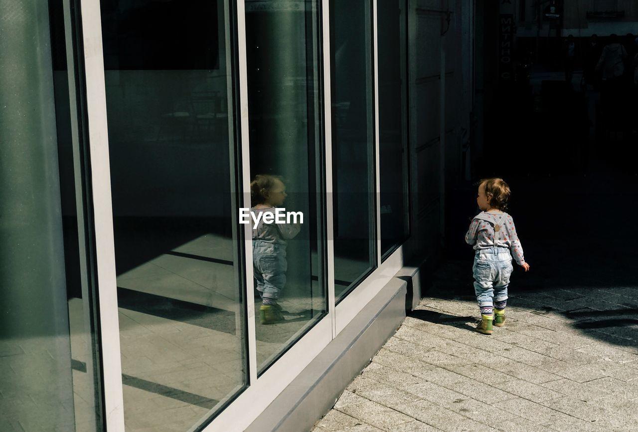 Rear View Of Child Walking By Door