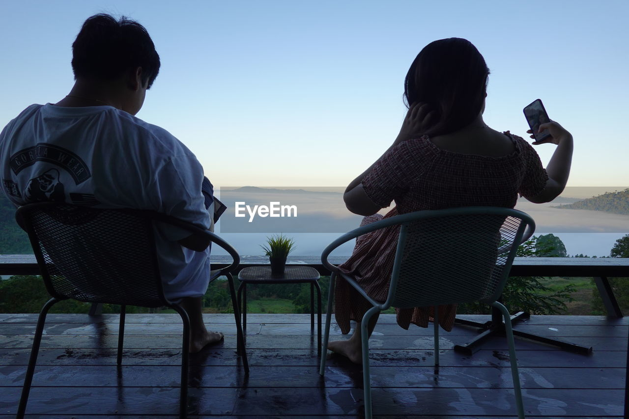 REAR VIEW OF COUPLE SITTING ON CHAIR AT SEA SHORE