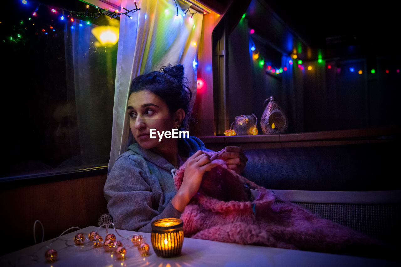 Young Woman Knitting Sweater While Sitting In Illuminated Caravan