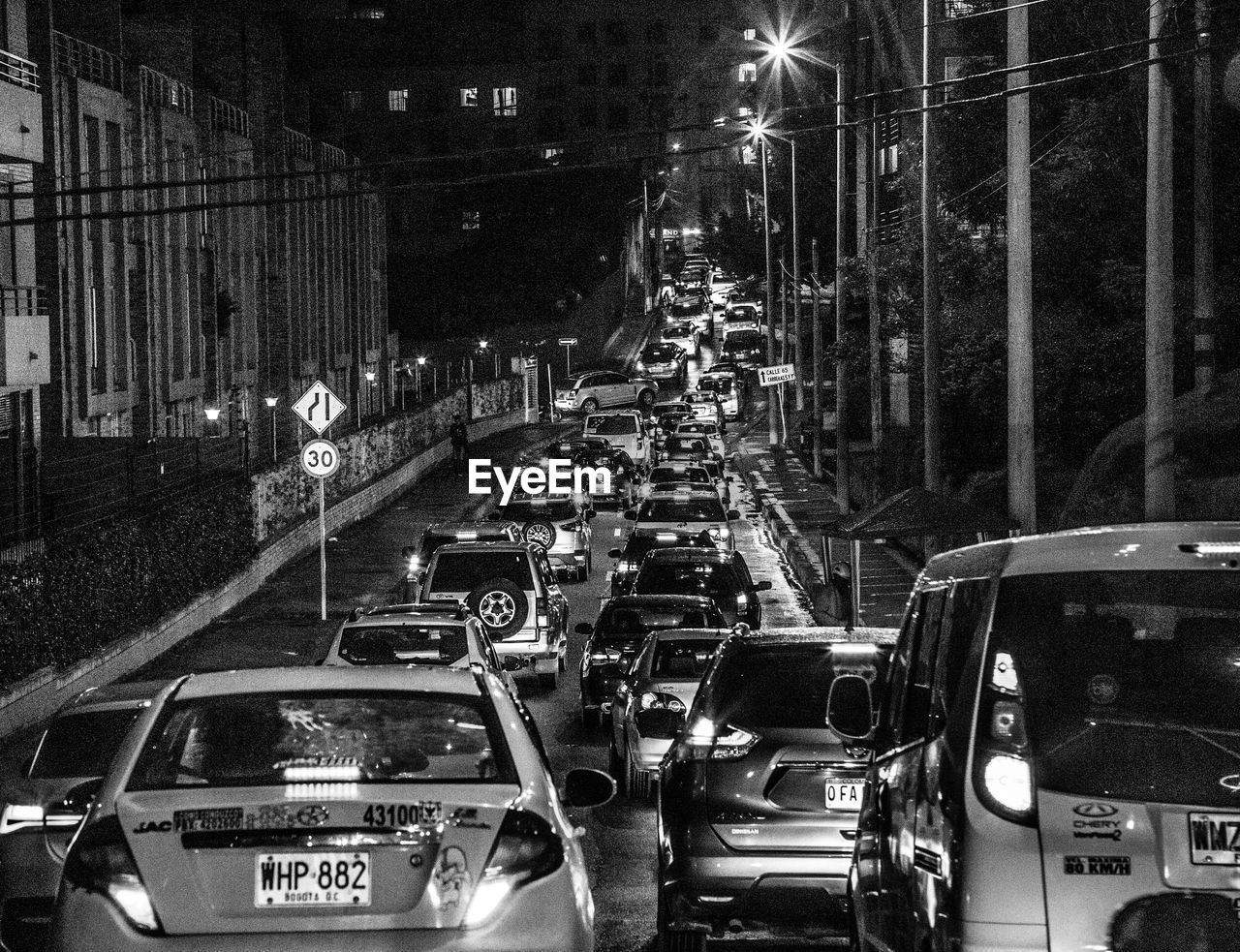 transportation, mode of transportation, car, land vehicle, motor vehicle, night, city, illuminated, architecture, built structure, street, traffic, no people, in a row, building exterior, city street, travel, road, outdoors