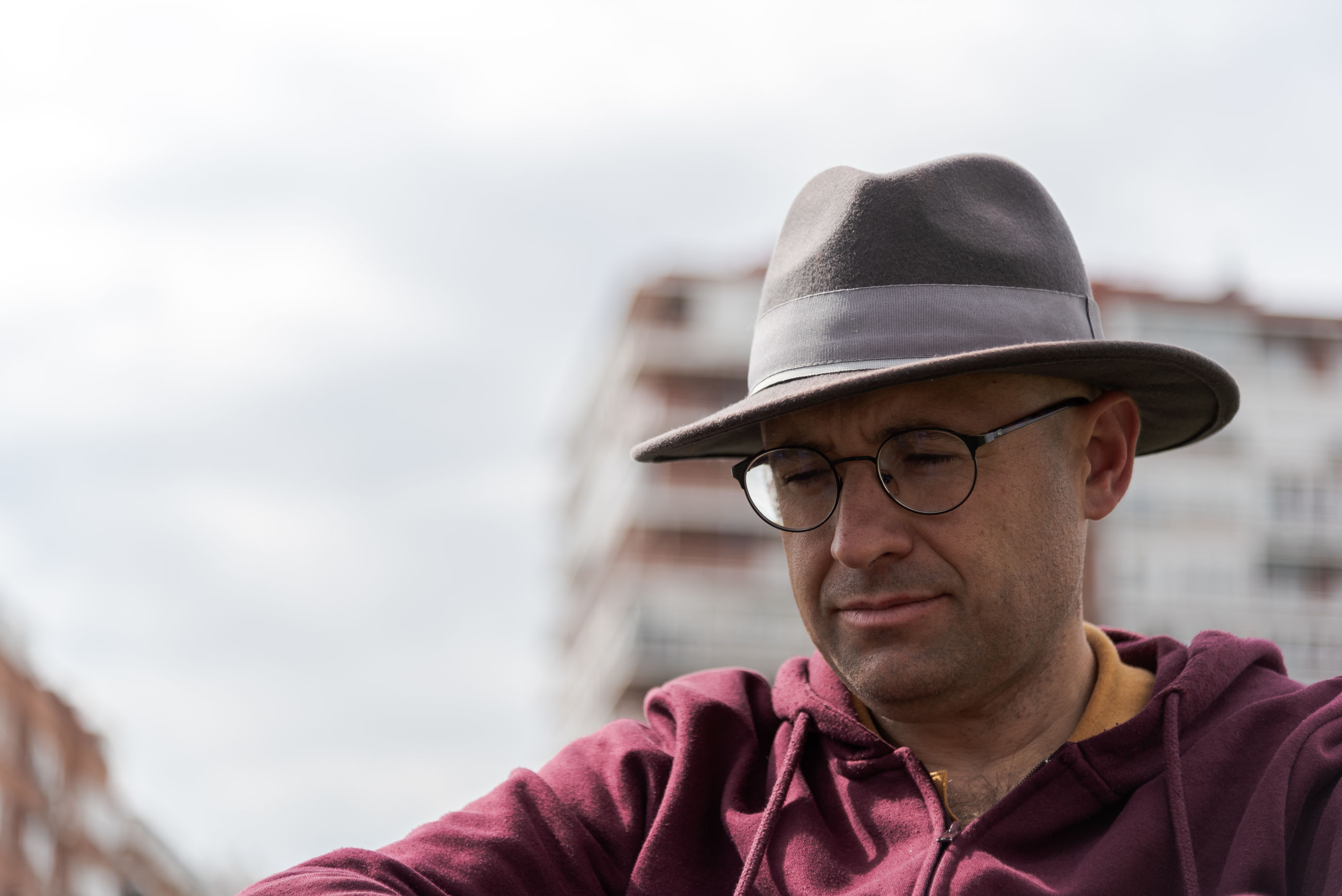 Close-up of mature man wearing eyeglasses and hat against sky