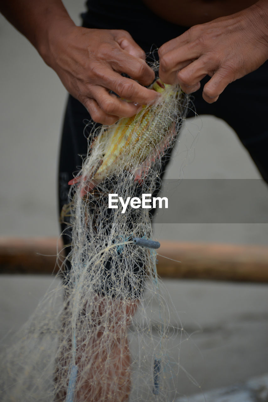 Close-Up Of Man Working On Fishing Net