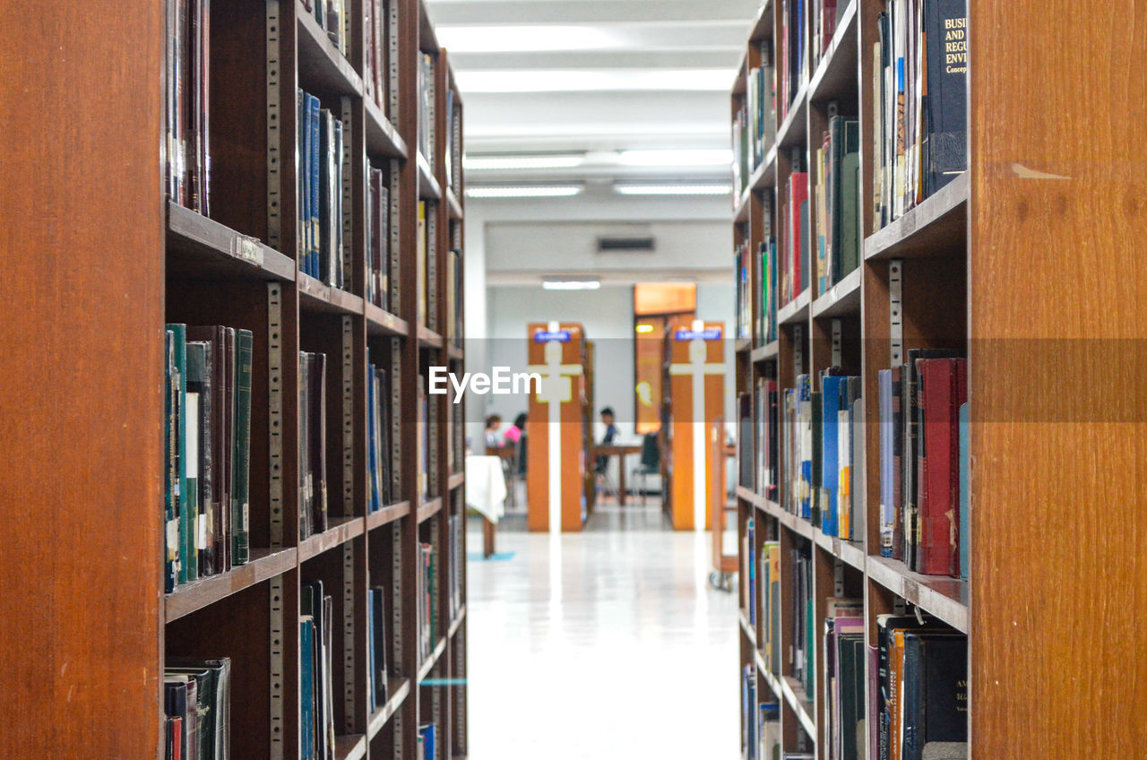 library, shelf, book, bookshelf, education, publication, school, university, learning, indoors, research, literature, large group of objects, wisdom, people, abundance, architecture, corridor, building, in a row, diminishing perspective, intelligence, order, studying, textbook, aisle