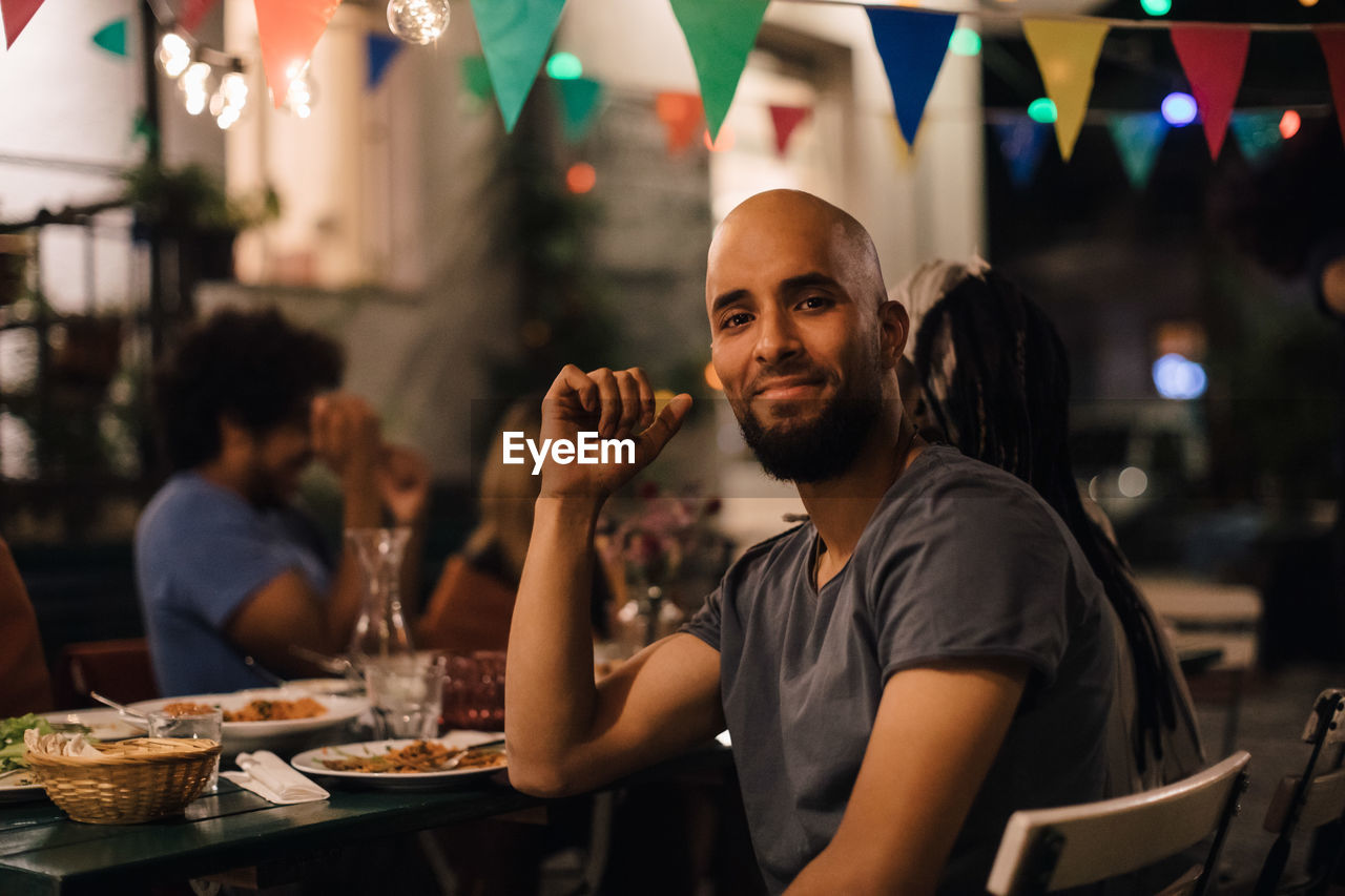 real people, portrait, smiling, young adult, food and drink, focus on foreground, restaurant, incidental people, happiness, men, drink, leisure activity, young men, emotion, looking at camera, lifestyles, casual clothing, table, business, refreshment, glass