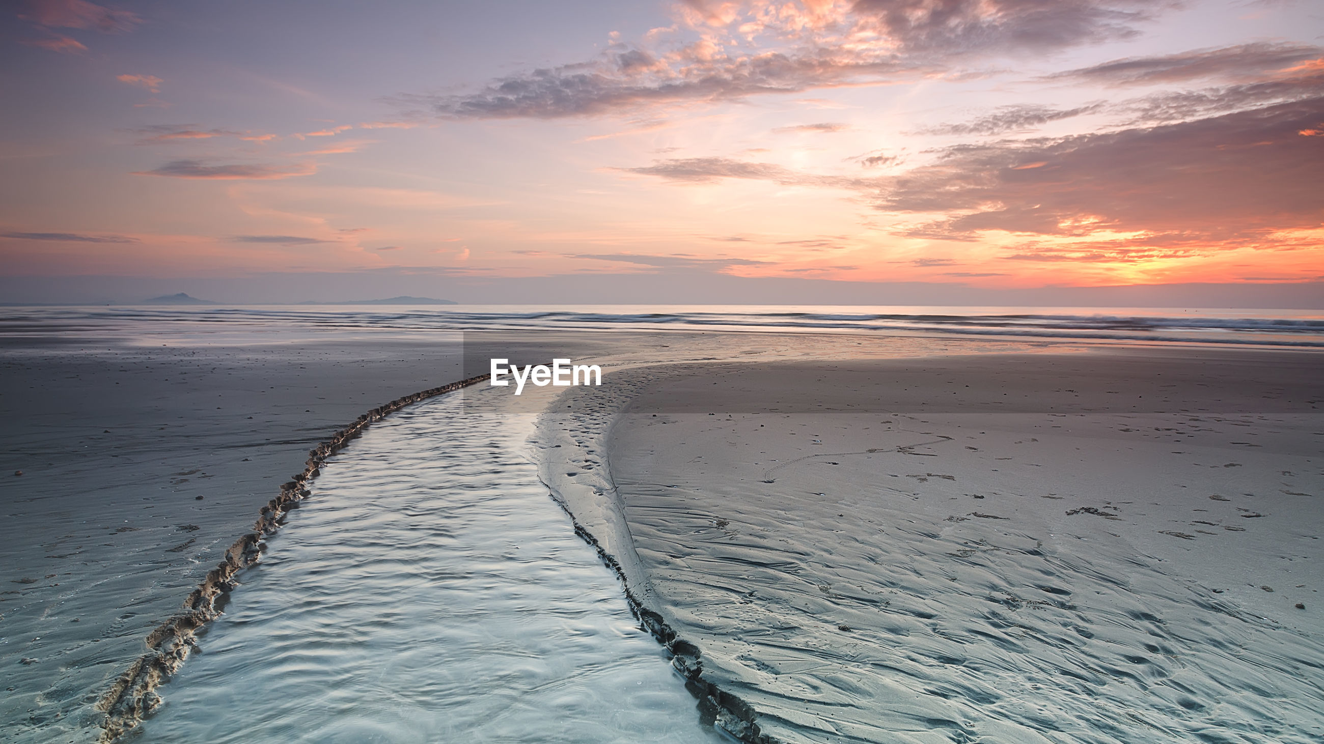 SCENIC VIEW OF BEACH AGAINST SKY AT SUNSET