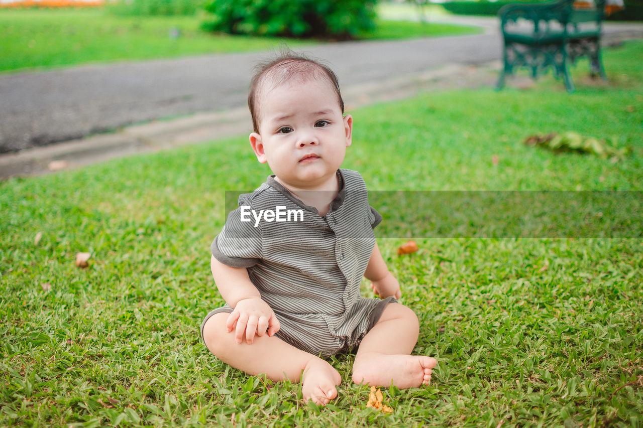 Portrait of cute toddler boy sitting in park
