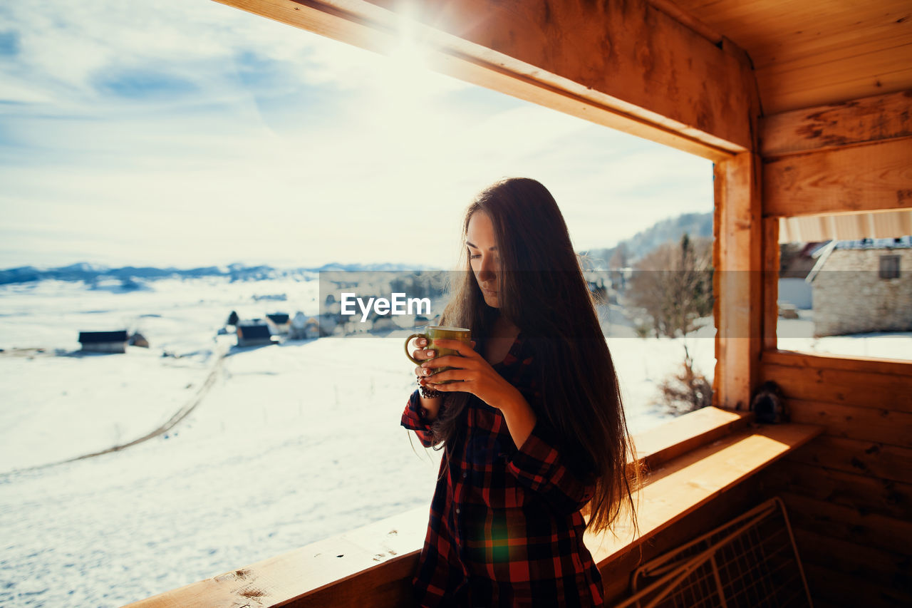 Portrait Of Young Woman Holding Cup While Standing By Window In Cottage During Winter