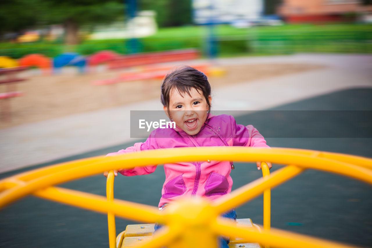 Portrait of happy girl sitting in outdoor play equipment