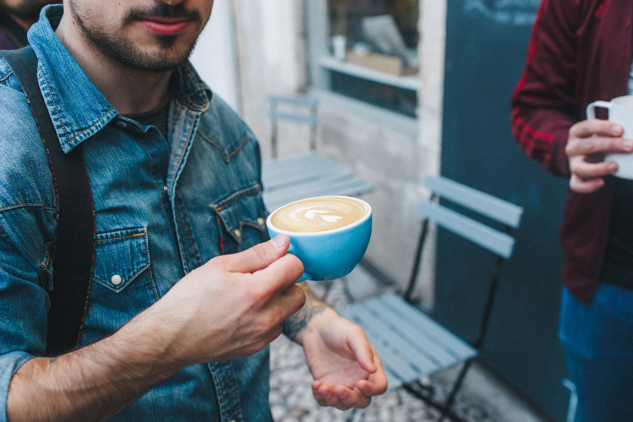 Midsection Of Young Man Holding Coffee Cup While Standing Outdoors