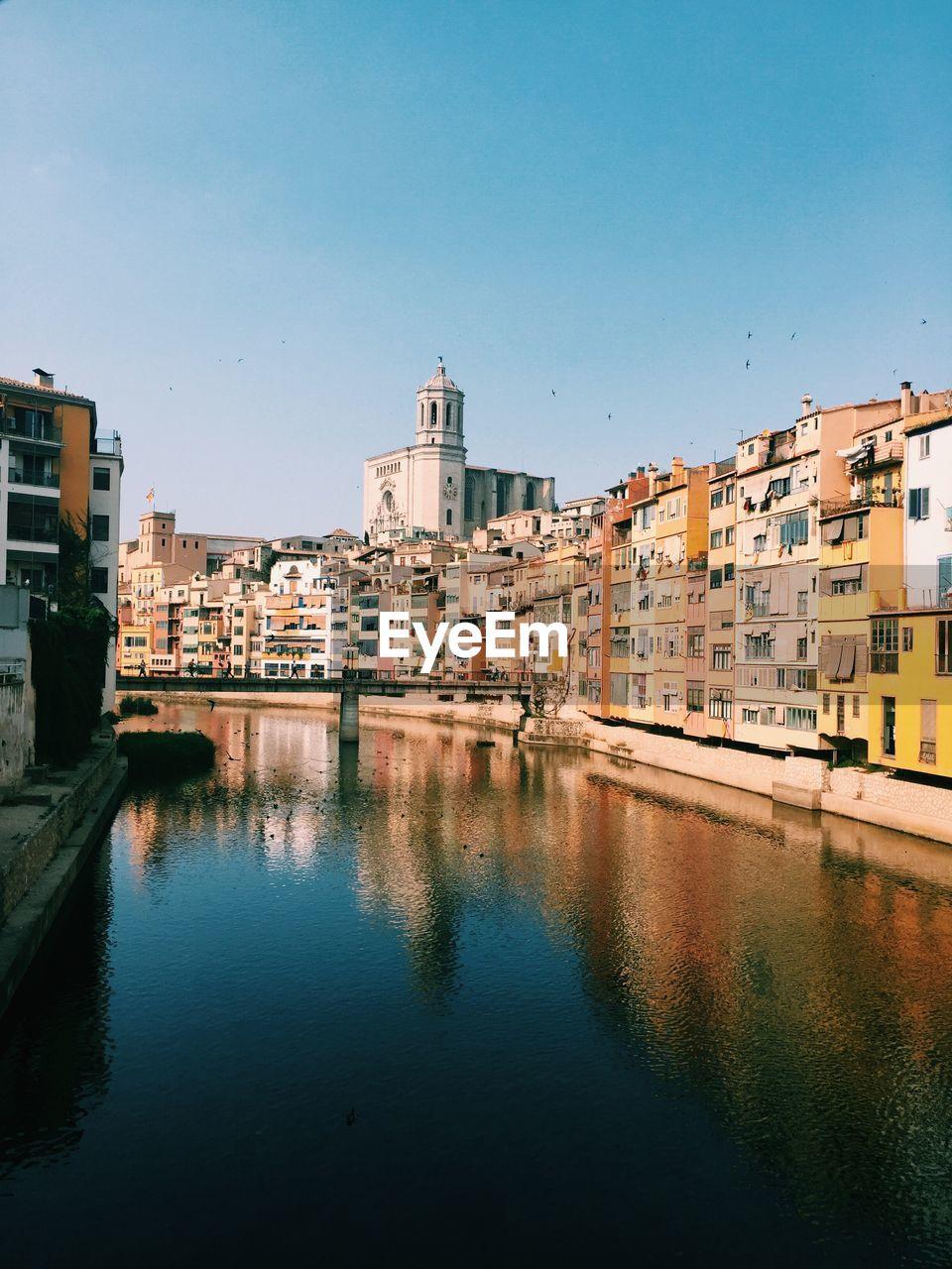 Onyar river amidst buildings against clear blue sky