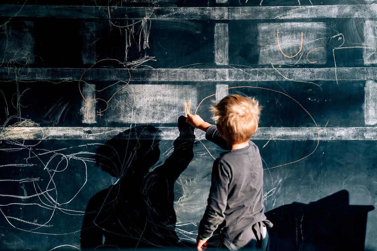 Rear view of boy writing on blackboard