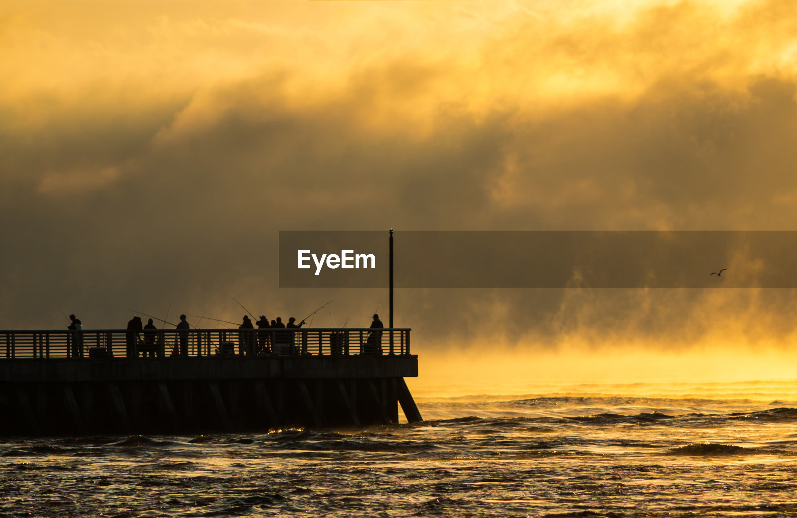 Silhouette people on pier at sea against sky during sunset