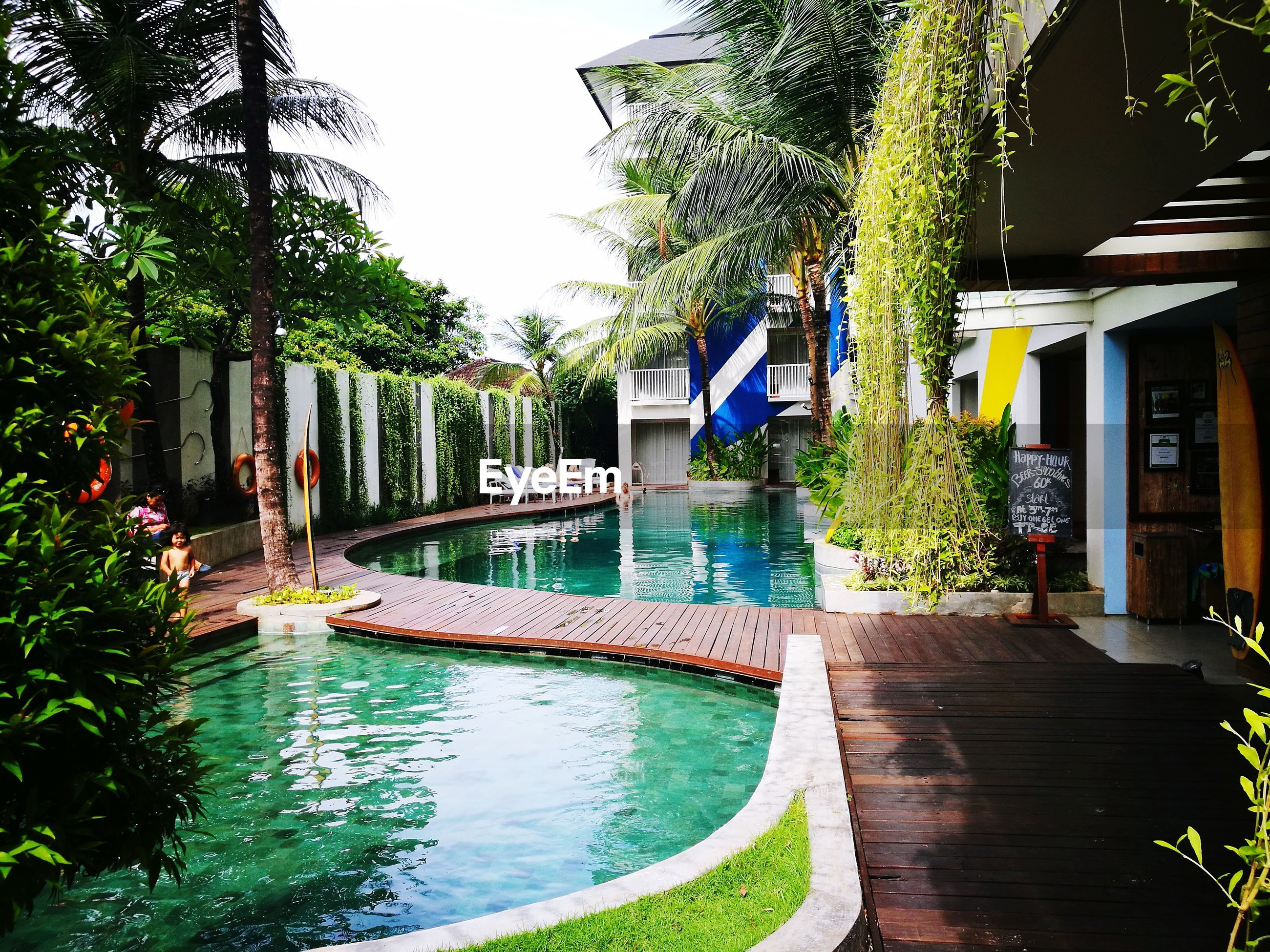 swimming pool, water, tree, palm tree, building exterior, architecture, tourist resort, growth, outdoors, built structure, day, vacations, luxury hotel, luxury, no people, plant, nature, beauty in nature, sky
