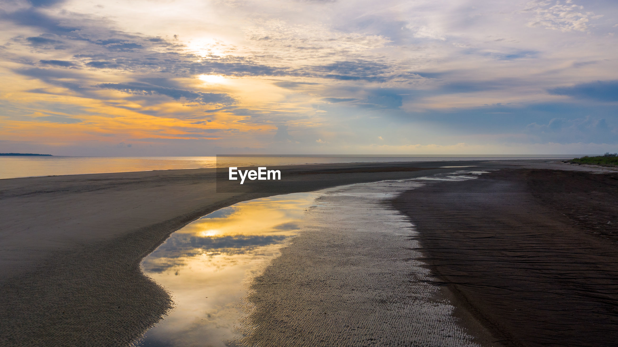 SCENIC VIEW OF WET BEACH AGAINST SKY DURING SUNSET