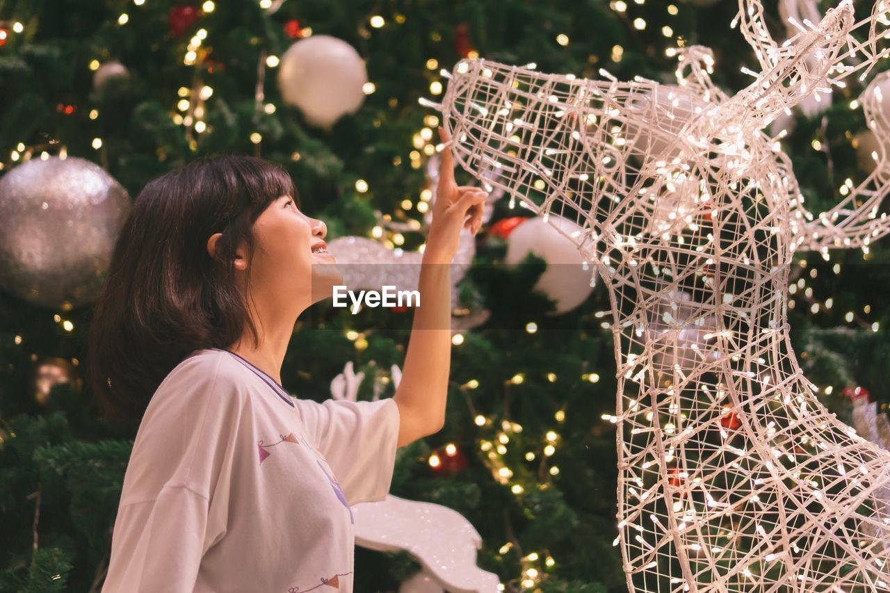 Side view of smiling girl looking at illuminated christmas decoration at home