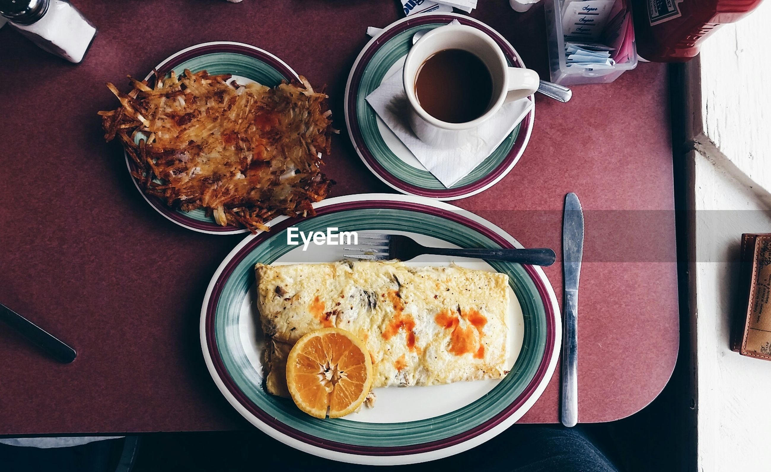 Directly above shot of egg omelet with coffee cup served on table