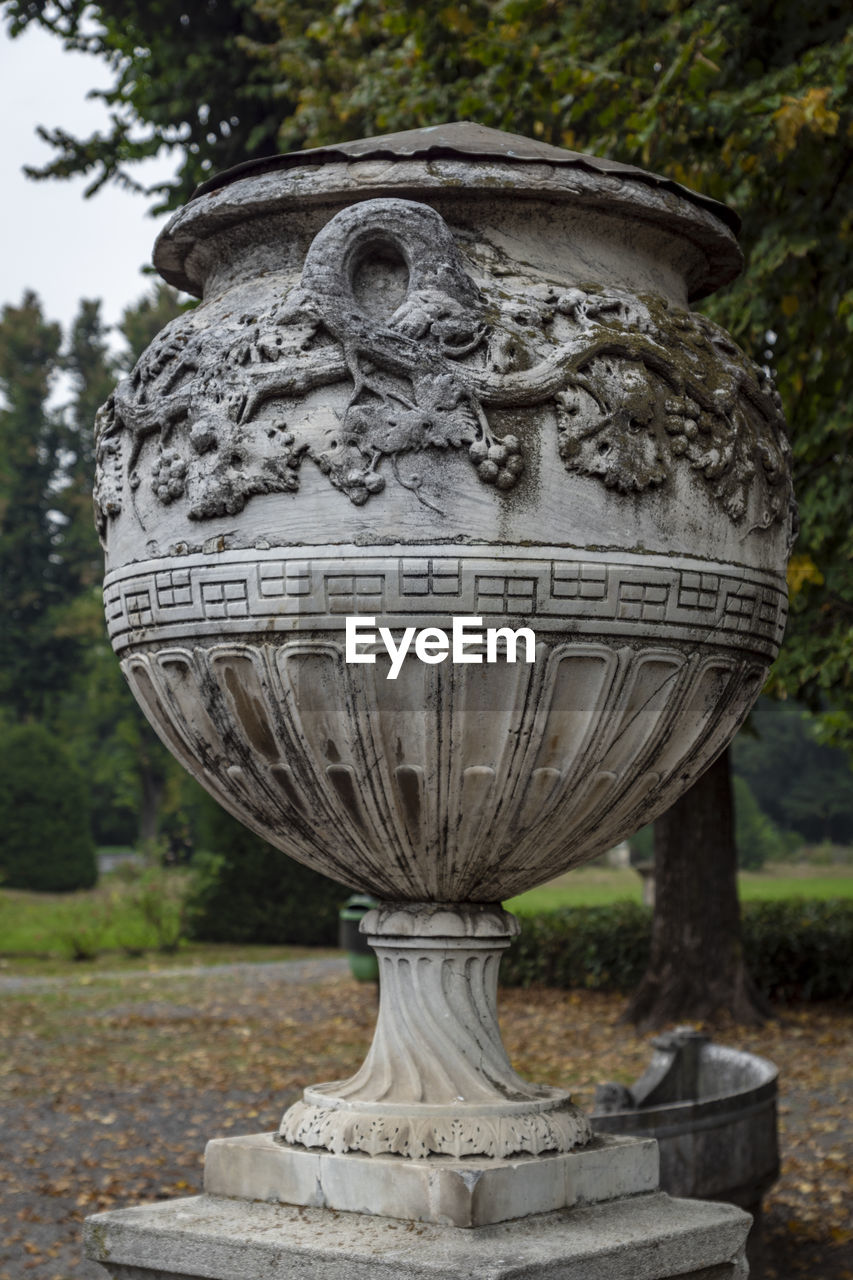 day, tree, plant, art and craft, no people, focus on foreground, sculpture, close-up, text, outdoors, stone material, nature, creativity, craft, decorative urn, metal, memorial, communication, park, carving - craft product, carving