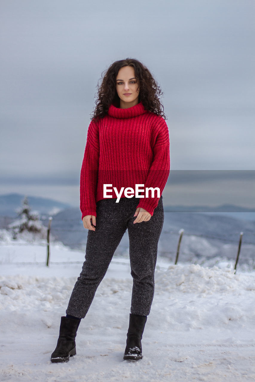 one person, young adult, red, standing, cold temperature, clothing, young women, full length, winter, lifestyles, land, beauty, leisure activity, front view, beautiful woman, looking at camera, portrait, real people, sea, warm clothing, hairstyle, outdoors